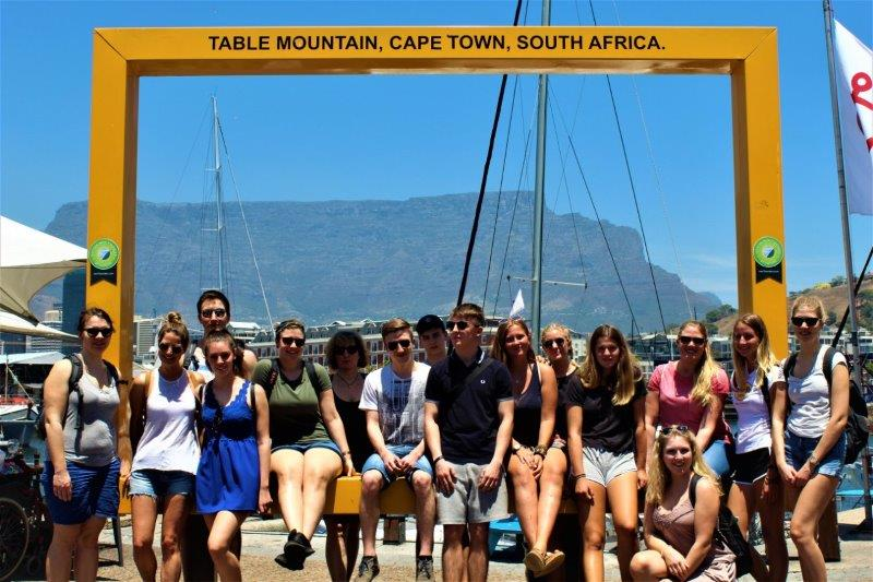 Tourists getting their picture taken at the table mountain frame in the Waterfront